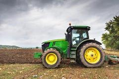 保加利亚- 2015年8月22th日, :耕与约翰Deere的一个领域 库存照片