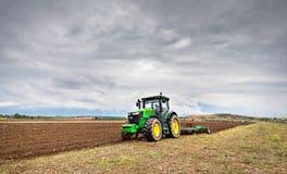 保加利亚- 2015年8月22th日, :耕与约翰Deere的一个领域 图库摄影
