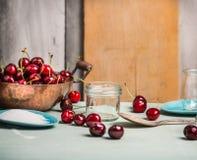 保存与在土气厨房用桌上的玻璃瓶子的樱桃莓果 免版税库存图片