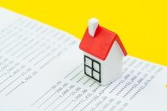 保存为第一个房子项目、抵押和房屋贷款或者不动产价格概念,有红色屋顶的微型房子在银行挽救 库存图片