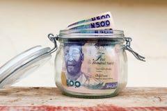 保存五百奈拉笔记储款刺激与黏附在开放瓶子的上面的外面有些笔记银行业务的,保险,储款 免版税库存图片