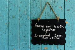 保存垂悬我们的地球的标志在门 免版税库存照片