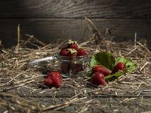保存瓶子在老木背景的草莓的玻璃 库存照片