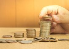 保存被预先设定的金钱概念用手投入金钱硬币堆gro 图库摄影