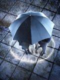 保护在一把伞以下的买卖人在雨中 图库摄影