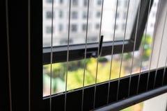 保护在被打开的区域的铁丝网在公寓的窗口 上升的孩子的预防  免版税库存照片