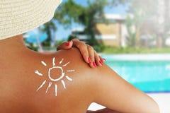 保护她的与太阳化妆水在游泳池,后面观点的少妇皮肤的一个无法认出的人 免版税库存照片