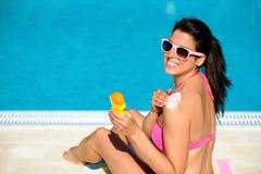 保护她的与遮光剂的妇女皮肤在夏天 免版税库存照片