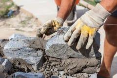 保护安装石头的黄色手套的瓦工工作者 免版税图库摄影