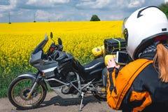 保护成套装备和玻璃的女孩与旅游摩托车 黄色花田 冒险足迹游览、enduro和路 免版税库存照片