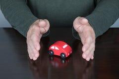 保护玩具汽车的人的手 免版税图库摄影