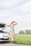 保护眼睛的妇女,当支持在乡下公路时的失败的汽车 库存图片