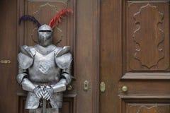 保护者-站立在一个老门前面的装甲的中世纪骑士 库存照片