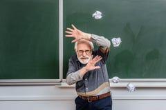 保护自己的资深讲师落的被弄皱的片断  图库摄影