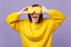 保持嘴的快乐的年轻女人开放,盖眼睛用在紫罗兰色柔和的淡色彩隔绝的新鲜的成熟橙色果子halfs  库存照片