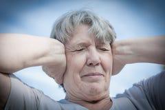 保持她的耳朵的妇女被关闭 免版税库存照片