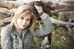 保持树枝的一名美丽的白肤金发的妇女,当坐的amonst开花时 免版税库存照片