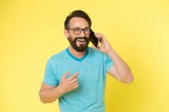 保持联系 人有胡子的快乐的成熟人举行手机黄色背景 行家智能手机电话伙伴 人 库存图片