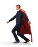 保持他的在一条无形的绳索的西装和红色海角的一个超级英雄平衡 库存照片