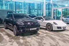 保时捷染黑Macan S和保时捷白色911 Carrera 4s 荷兰男人飞行堡垒保罗・彼得・彼得斯堡餐馆俄国圣徒 2018年3月02日 免版税图库摄影