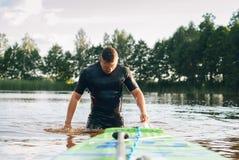 保温潜水服的一个人从水涌现, 免版税库存照片
