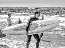 保温潜水服的一个人有一个冲浪板的在海滩的一个晴天 免版税库存图片