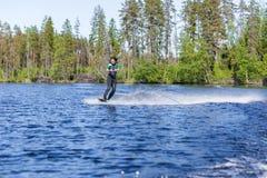 保温潜水服骑马wakeboard的年轻俏丽的亭亭玉立的深色的妇女在汽艇波浪  库存照片