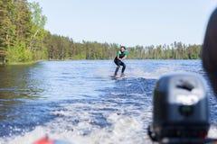 保温潜水服骑马wakeboard的年轻俏丽的亭亭玉立的深色的妇女在汽艇波浪  免版税库存照片