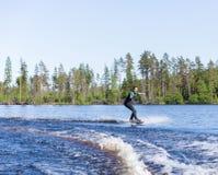 保温潜水服骑马wakeboard的年轻俏丽的亭亭玉立的深色的妇女在汽艇波浪  免版税图库摄影