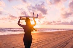 保温潜水服的美丽的少妇海浪女孩有在一个海滩的冲浪板的在日落或日出和海洋 库存图片