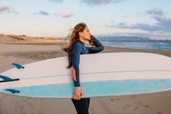 保温潜水服的运动的海浪妇女在日落或日出在海洋 免版税库存图片