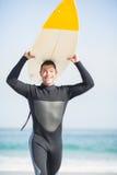 保温潜水服运载的冲浪板天花板的愉快的人 库存图片