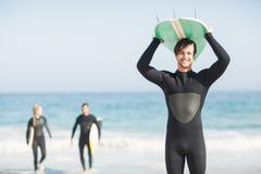 保温潜水服运载的冲浪板天花板的愉快的人 免版税图库摄影
