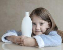 保留不同的白色秀丽化妆品的逗人喜爱的小女孩在她的手,看照相机 婴孩浴,卫生学辅助部件 库存照片