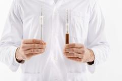 保留两个小瓶液体的人 免版税库存照片