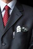 保留两个电灯泡-白炽和萤光节能的典雅的时髦的商人-在他的衣胸袋 库存图片