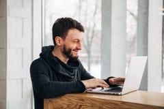 保留他的在普通便携式计算机键盘的愉快的年轻有胡子的学生手,当研究文凭项目时 免版税库存照片
