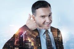 保留他的手的微笑的经理在耳朵附近 免版税库存照片