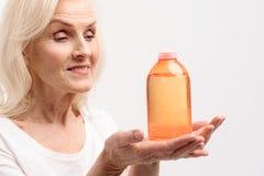 保留化妆用品的愉快的微笑的老妇人 图库摄影