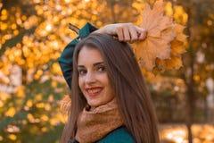 保留在她的头上的叶子并且对krupnyy计划微笑一个美丽的迷人的女孩的画象 免版税库存图片
