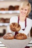 保留在餐巾的女服务员面包在面包店柜台 免版税图库摄影