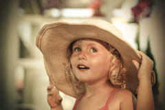 保留她的大帽子的微笑的蓝眼睛的白肤金发的小女孩 库存图片