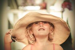 保留她的大帽子的微笑的蓝眼睛的白肤金发的小女孩 免版税库存照片