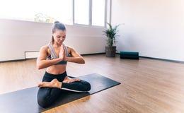 保留适合的适合的妇女通过做瑜伽 免版税图库摄影