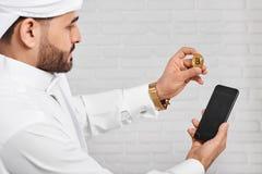 保留金黄bitcoin和手机的阿拉伯商人 免版税图库摄影