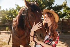保重和拥抱她的马的年轻女牛仔在大农场 库存照片