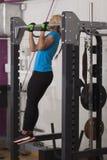 保镖 坚强的适合妇女行使在健身房的-做引体向上 库存图片