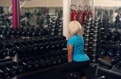 保镖 强的适合女性行使与重量 白肤金发的在健身房的女孩举的重量 坚强的妇女 图库摄影