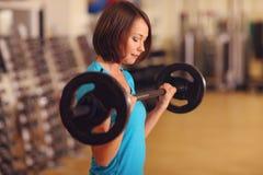 保镖 行使与在健身类的杠铃的妇女 在健身房的女性锻炼与杠铃 库存照片
