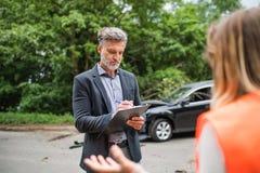 保险代理公司谈话与一名妇女外面路的在车祸以后 库存图片